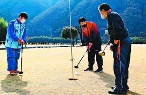 美馬市パークゴルフガイドクラブのメンバー(右)とラウンドする生徒=同市美馬町の吉野川河畔ふれあい広場パークゴルフ場