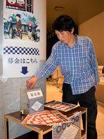 上映前に寄付金を贈る来場者=徳島市の県立21世紀館