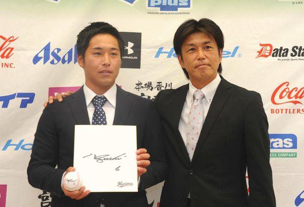 ロッテの黒木スカウト(右)から渡された井口監督の色紙とサインボールを手にする鎌田=徳島市のとくぎんトモニプラザ