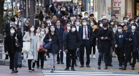 マスク姿で帰宅する人たち=3日夕、東京・新宿