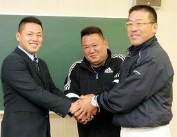 巨人から育成ドラフト7位で指名され、握手を交わす(左から)折下、父龍也さん、中山監督=新野高