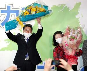 福岡県知事選で初当選を決め、花束を手に笑顔の服部誠太郎氏(左)=11日夜、福岡市