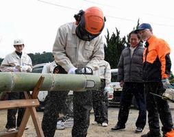 小島理事長(右から2人目)の指導でチェーンソーで竹を切る阿南工業高の生徒=阿南市新野町