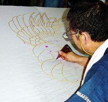 筒描の技法で図柄を描く古庄さん=徳島市南佐古六番町の工房(市教委提供)