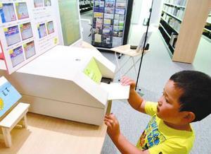 専用端末で「読書の記録」に印字する子ども=吉野川市鴨島町の鴨島図書館