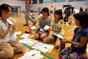 紙飛行機を作りながら交流する児童ら=美波町の日和佐総合体育館