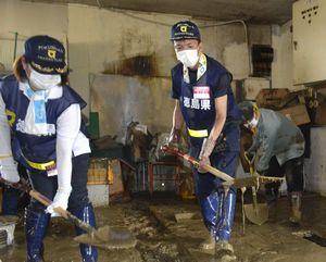 堆積した泥を倉庫外へかき出す徳島県職員ら=福岡県朝倉市菱野地区
