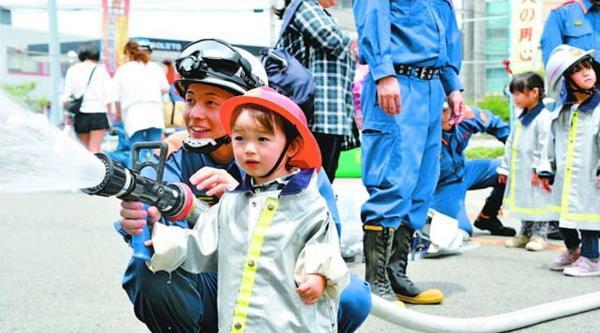 消防署員と一緒に放水体験する子ども=鳴門市撫養町南浜の市消防本部