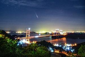 岡山県倉敷市で撮影された「ペルセウス座流星群」の流れ星。中央は瀬戸大橋=13日午前3時27分(倉敷科学センターの三島和久学芸員提供)