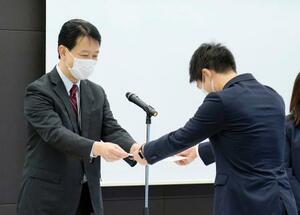東京都千代田区の三井物産本社で行われた内定式で、内定通知書を受け取る男性=1日午前