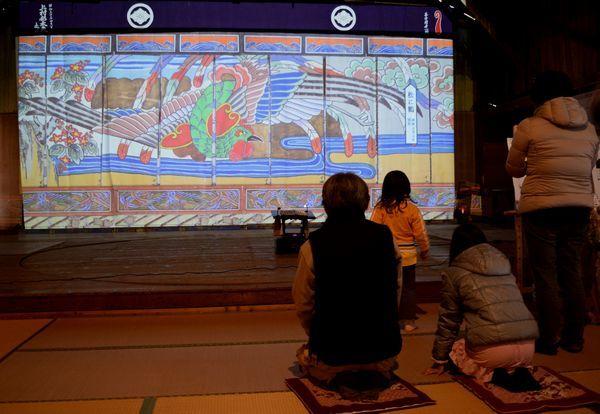 画面に映し出された襖絵が動く様子を観賞する来場者=神山町神領の劇場寄井座