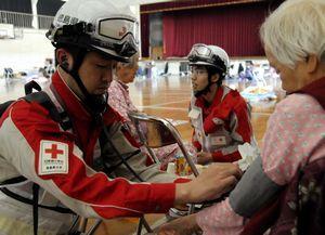 避難者(右)の血圧を測る徳島赤十字病院の災害救護班メンバー=熊本市中央区の熊本国府高
