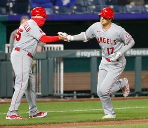 ロイヤルズ戦の5回、本塁打を放ち三塁コーチ(左)とタッチを交わすエンゼルス・大谷=カンザスシティー(共同)