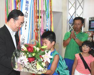 飯泉知事(左端)から花束を受け取る加藤君=鳴門市鳴門町の渦の道
