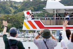 聖火を収めたランタンを手に、遊覧船に乗って松島湾を移動する聖火ランナー(奥左端)=20日午後、宮城県松島町