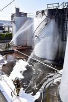 爆発した石油タンク㊨の消火に当たる消防隊員=午前8時5分ごろ、徳島市末広1