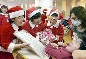 サンタにふんしたマラソン愛好家からプレゼントを受け取る子ども=小松島市中田町のひのみね総合療育センター