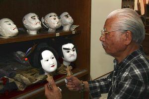 修復した三千良の頭を手に取る甘利さん。7月に披露される=美波町奥河内の日和佐図書・資料館