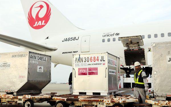 日本航空の旅客機から運び出されるイオングループの支援物資=松茂町の徳島阿波おどり空港