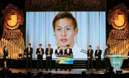 Jリーグ年間表彰式で最優秀選手賞を受賞し、あいさつする横浜Mの仲川輝人。E―1選手権開催地の韓国・釜山から中継でスクリーンに映し出された=8日、東京都内のホテル