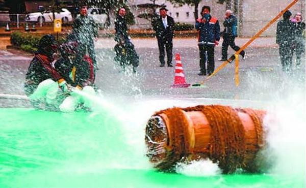 水を当ててたるを回転させる消防団員=三好市の池田総合体育館駐車場