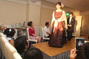 ファッションショーに参加し、笑顔で花道を歩く母親=徳島グランヴィリオホテル