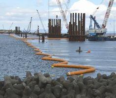 橋梁工事が進む現場。海面の黄色の浮きから約2~5メートルの深さまで汚濁防止フェンスがつり下げられている=徳島市の吉野川河口
