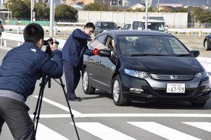 交通マナー向上に向けて啓発動画を撮影する警察官=松茂町の県警運転免許センター