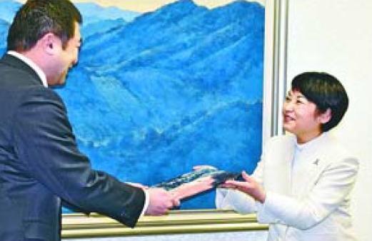 原井市長に絵本を手渡す髙橋理事長(右)=吉野川市役所