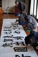 敦賀気比高の受け入れを前に、看板を作る地元住民ら=阿南市山口町の桑野公民館