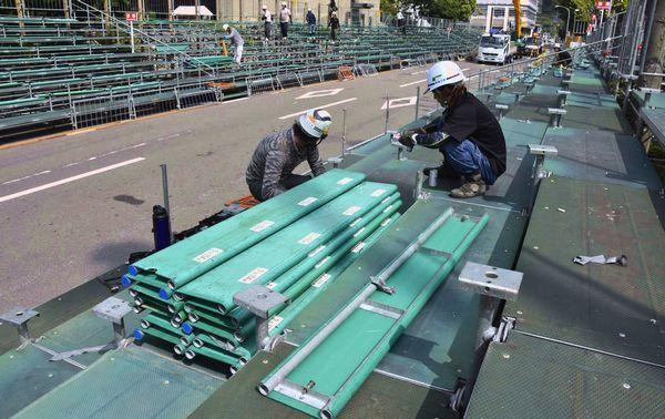 市役所前演舞場の座席板を取り外す作業員=徳島市幸町2