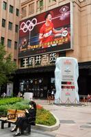 東京五輪のニュースを伝える北京市内の大型画面。下は北京冬季五輪のカウントダウンタイマー=3日(共同)
