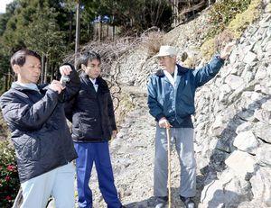 高開さん(右)の説明を受けながら、石積みを視察する熊本県職員=吉野川市美郷大神
