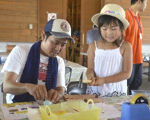 木工時計を作る親子=鳴門市鳴門町の鳴門ウチノ海総合公園
