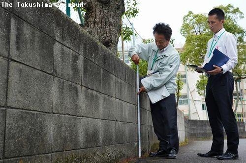 学校のブロック塀を点検する鳴門市教委職員=同市の黒崎小学校