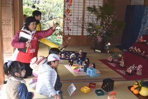 森本家住宅でひな人形について説明するボランティアガイド=勝浦町坂本