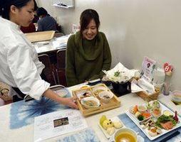 上勝町産つまものや旬の野菜を使った料理を提供する生徒(左)=小松島西高