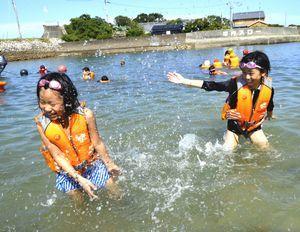 友達同士で水を掛け合うなどして、海に親しんだ小学生=牟岐町沖の出羽島