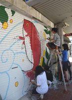 商店街のシャッターに絵を描く高校生=鳴門市の大道商店街