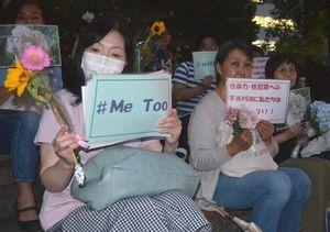 プラカードを持ち、無罪判決の不当性や性暴力撲滅を訴えるフラワーデモの参加者=11日、神戸市の東遊園地