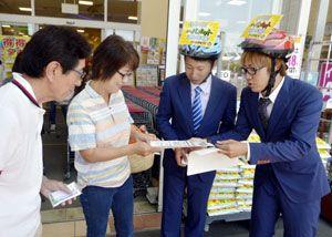 自転車用のヘルメットをかぶって買い物客に啓発チラシを手渡すキャンパスボーイの2人=徳島市西新浜町の量販店