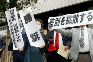 被差別部落の地名リストを巡る訴訟の判決を受け、東京地裁前で「勝訴」などと書かれた紙を掲げる弁護士ら=27日午後