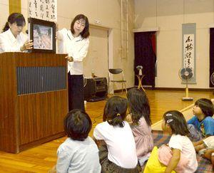 米貨物船の乗組員を救助する様子を描いた紙芝居を見る子どもたち=美波町の志和岐定住促進センター