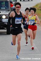 招待選手の上野さん(左)が女子区間で快走する=1月4日、小松島市江田町