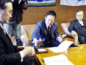 メディアドゥテック徳島の操業に向けて覚書に調印する藤田社長(中)と飯泉知事(左)=県庁