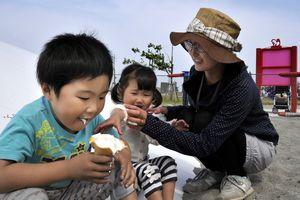 強い日差しの下、ソフトクリームを食べる男の子=松茂町の月見ケ丘海浜公園