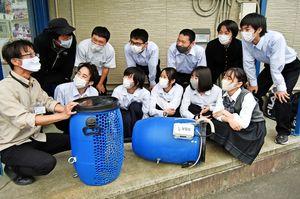佐藤代表(左端)から浄化装置の製作方法などを聞く高校生=小松島市金磯町