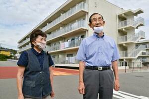 東京電力福島第1原発事故で復興公営住宅(後方)での避難生活が続く志賀文清さん(右)夫妻=16日午前10時ごろ、福島県いわき市