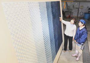 藍染の阿波和紙を使った壁紙の仕上がりを確認する美恵子さん(左)ら=吉野川市山川町の阿波和紙伝統産業会館