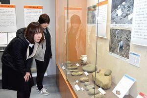 辰砂を採取するために使った石杵を見る来館者=阿南市文化会館
